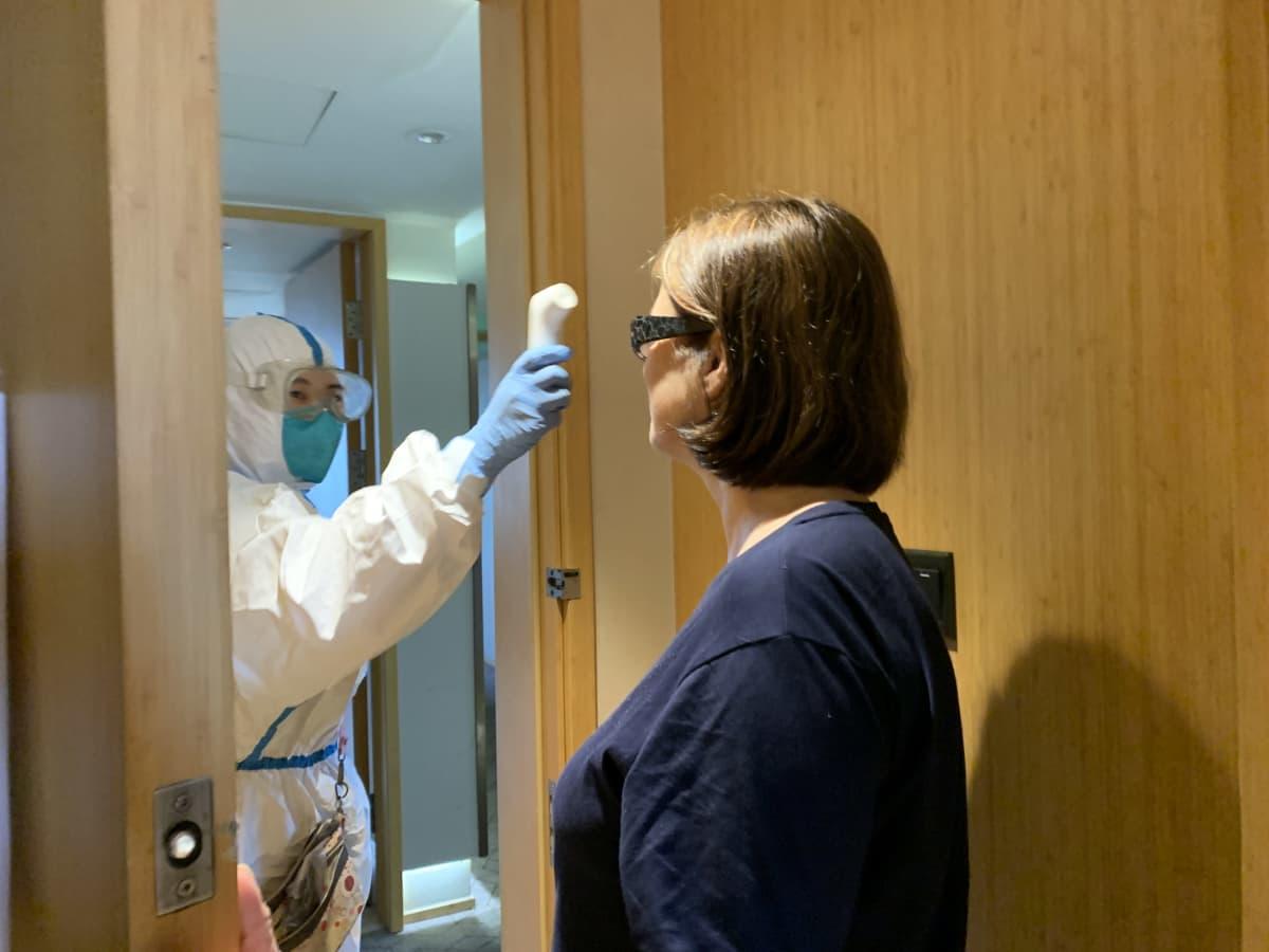 kiinalainen hoitaja valkoisessa suojapuvussa mittaa kehon lämpötilaa etäkuumemittarilla hotellihuoneen ovella Shanghaissa koronaviruskaranteenissa Kirsi Crowleylta