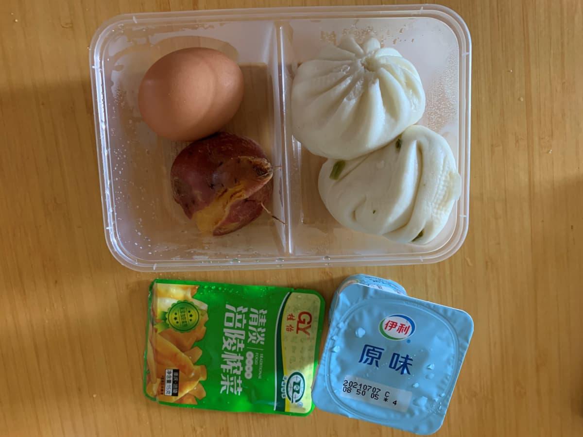 muovipakkauksessa oleva aamiainen koronaviruskaranteenissa. Pakkauksessa on keitetty kananmuna, puolikas keitetty bataatti, kaksi pyöreää baozi-nyyttiä. vierellä yksittäispakattu sinappipikkelsipussi ja juomajugurttipurkki.