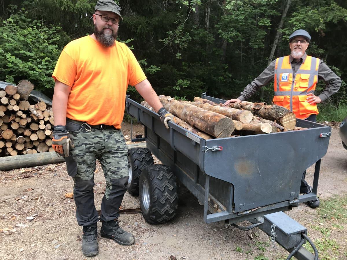 Metsähallituksen työntekijät poseeraavat polttopuulastin kanssa.