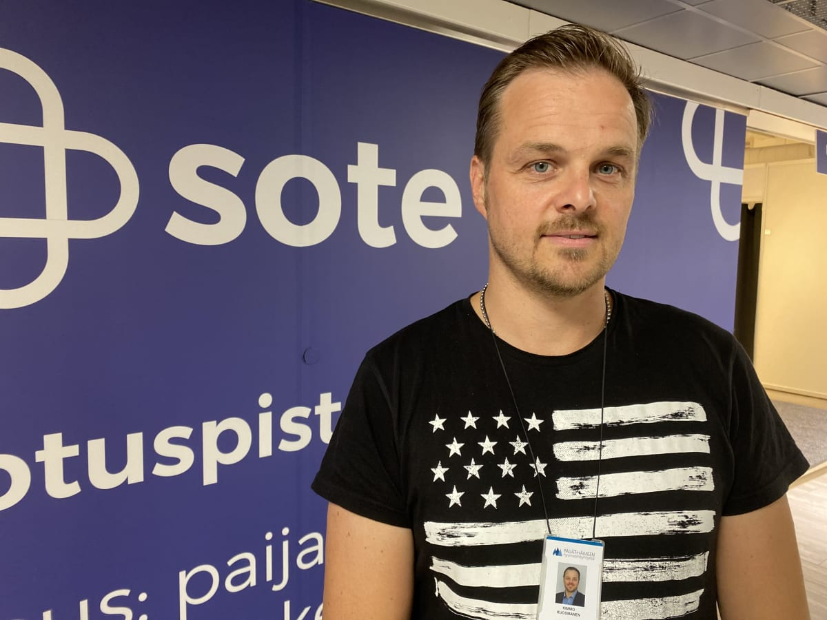 Kimmo Kuosmanen katsoo kameraan, Päijät-Soten mainoslakana taustalla