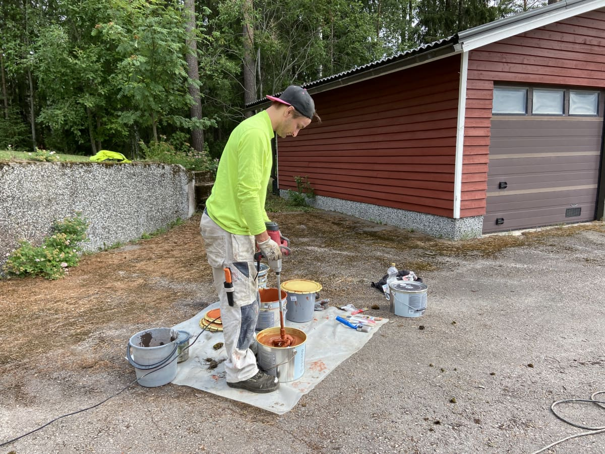 Maalari Maksi Salminen vatkaa maalia maalipurkissa työkohteen pihalla