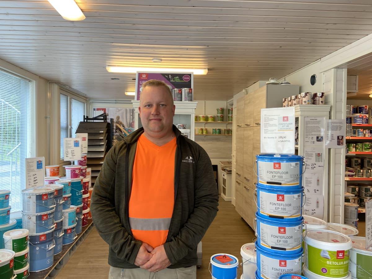 Jämsän Maalaus ja Kunnostus Oy:n toimitusjohtaja Teemu Hannula seisoo maalimyymälässään maalipurkkien keskellä