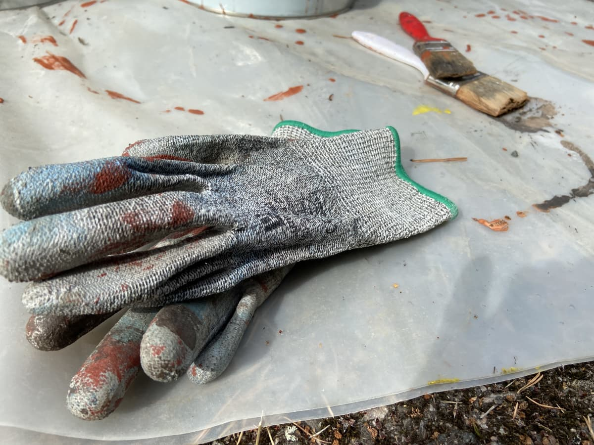 Maalauskäsineet makaavat maassa muovin päällä