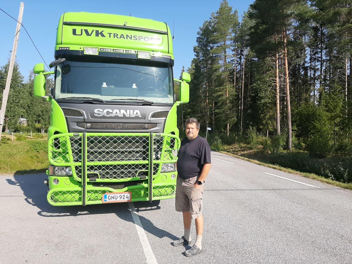 En man i shorts står framför en grön lastbil.
