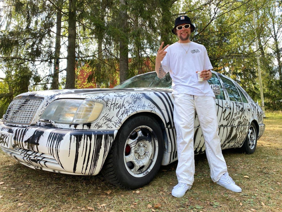 Taiteilija Sheikki keravalaisen purkutaidetalon pihalla oman Mercedes-Benz-autonsa edessä.
