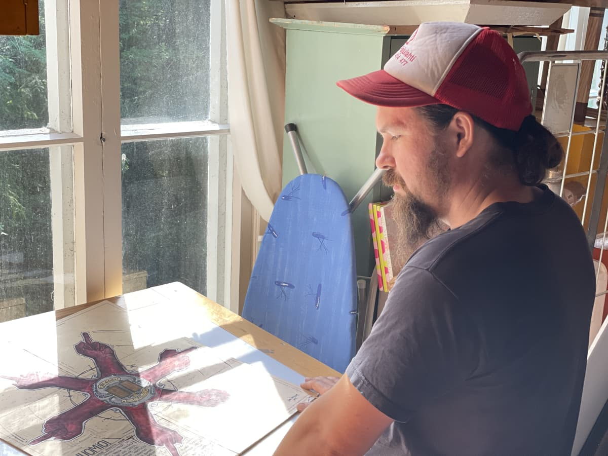 Joona Hamm seisoo ikkunan edessä ja katsoo pöydällä olevaa työtään.