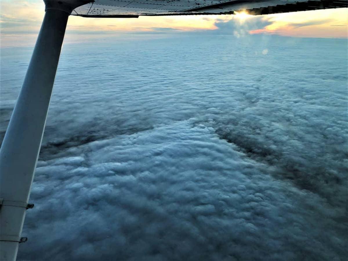 Näkymä pilvien yläpuolelta, alla näkyy metsäpalon pilvikerrokseen synnyttämiä juopia.