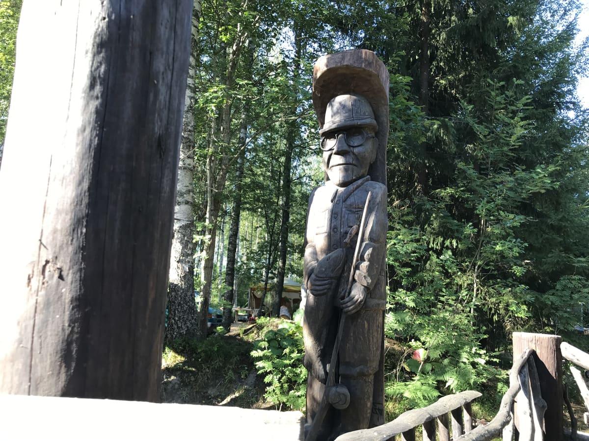 Seppo Laatusen puuveistos, joka esittää Urho Kekkosta onki ja kala kädessä.