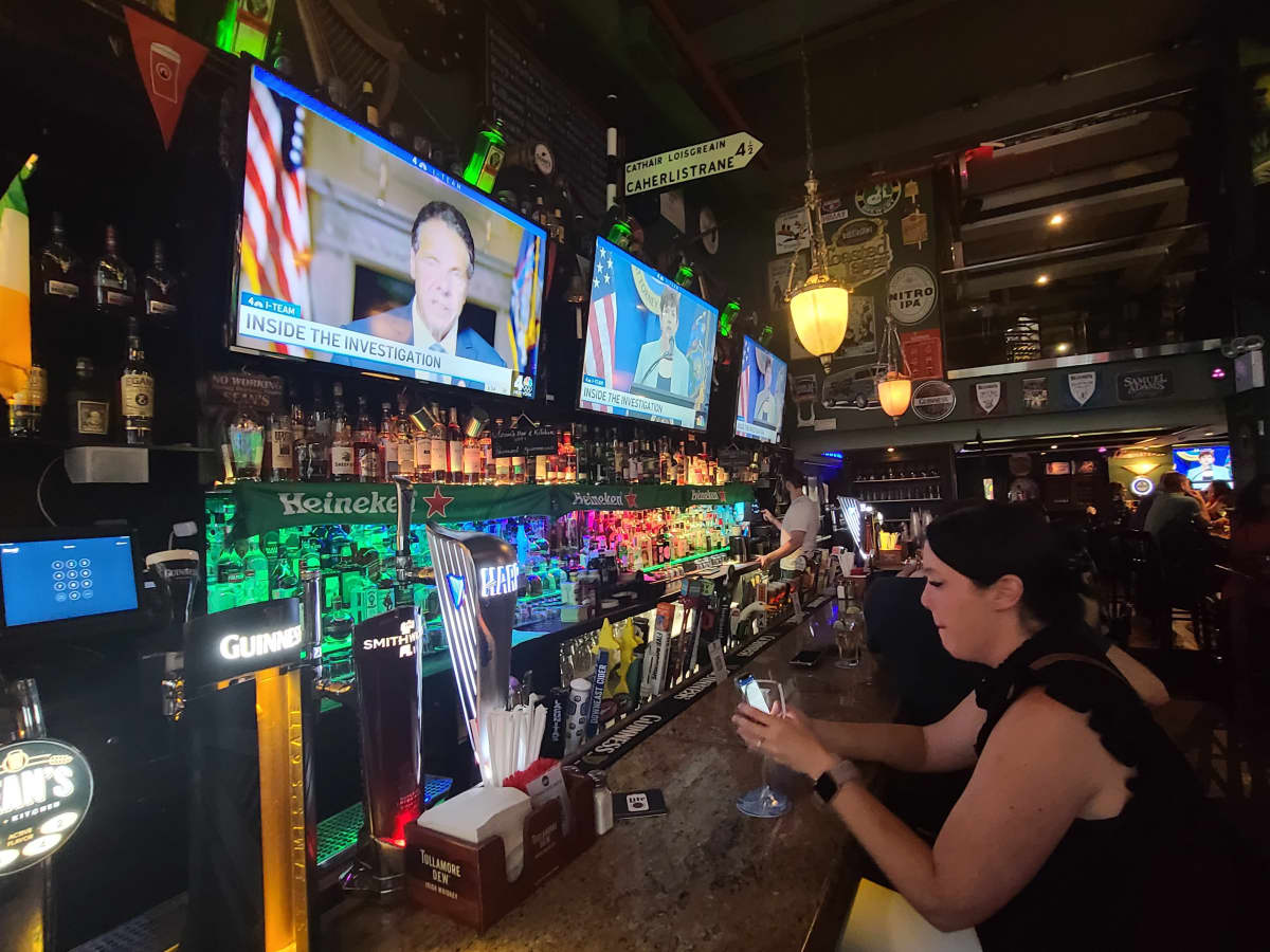 Nainen istuu tiistaina Sears-baarissa New Yorkissa samalla, kun Cuomoa koskeva tiedotustilaisuus on meneillään televisiossa.
