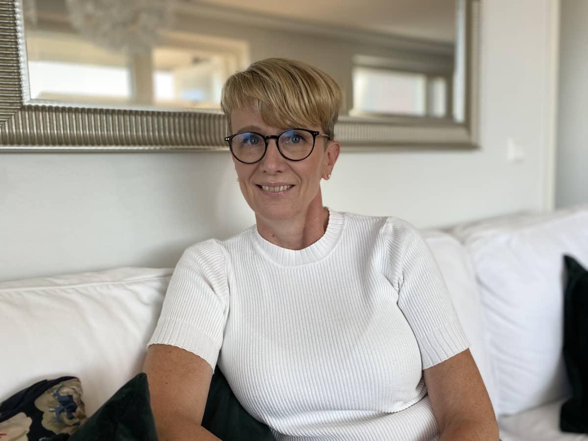 Voimavaravalmentaja Ann-Mari Nordenswan istuu sohvalla.