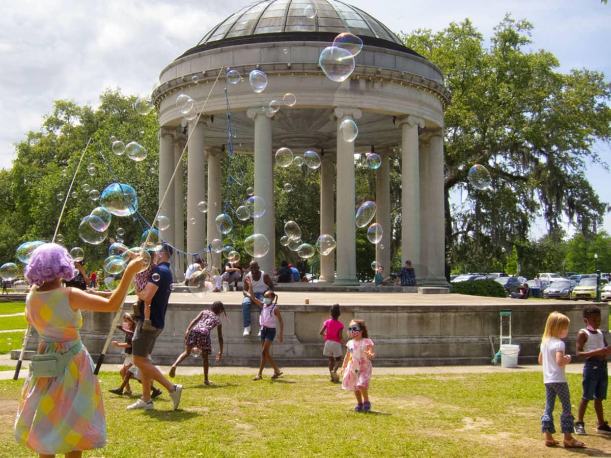 Lapset tavoittelev at isoja saippuakoia, joita selin seisova nainen heille tekee. Takana kupolikattoinen paviljonkirakennus.