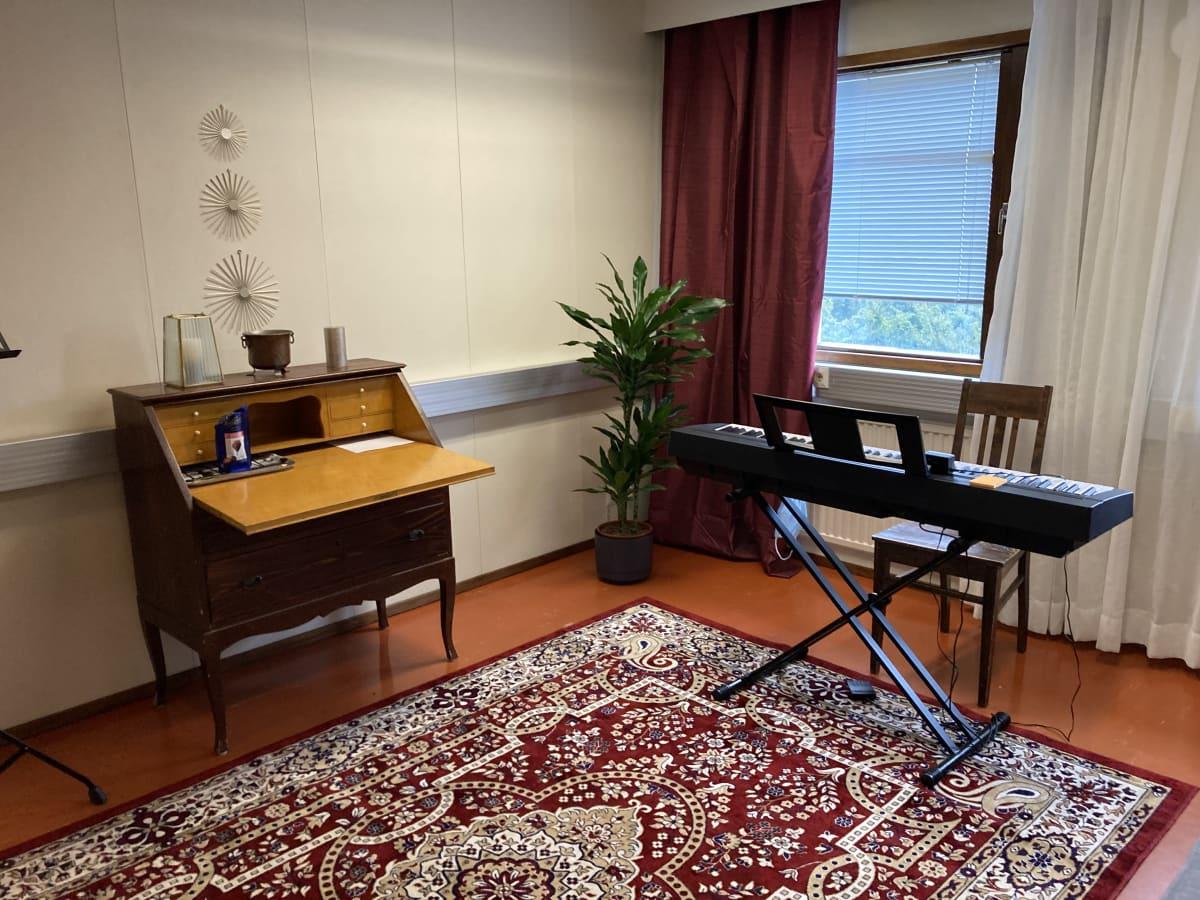 huone jossa on sähköpiano ja lipasto punaisella matolla