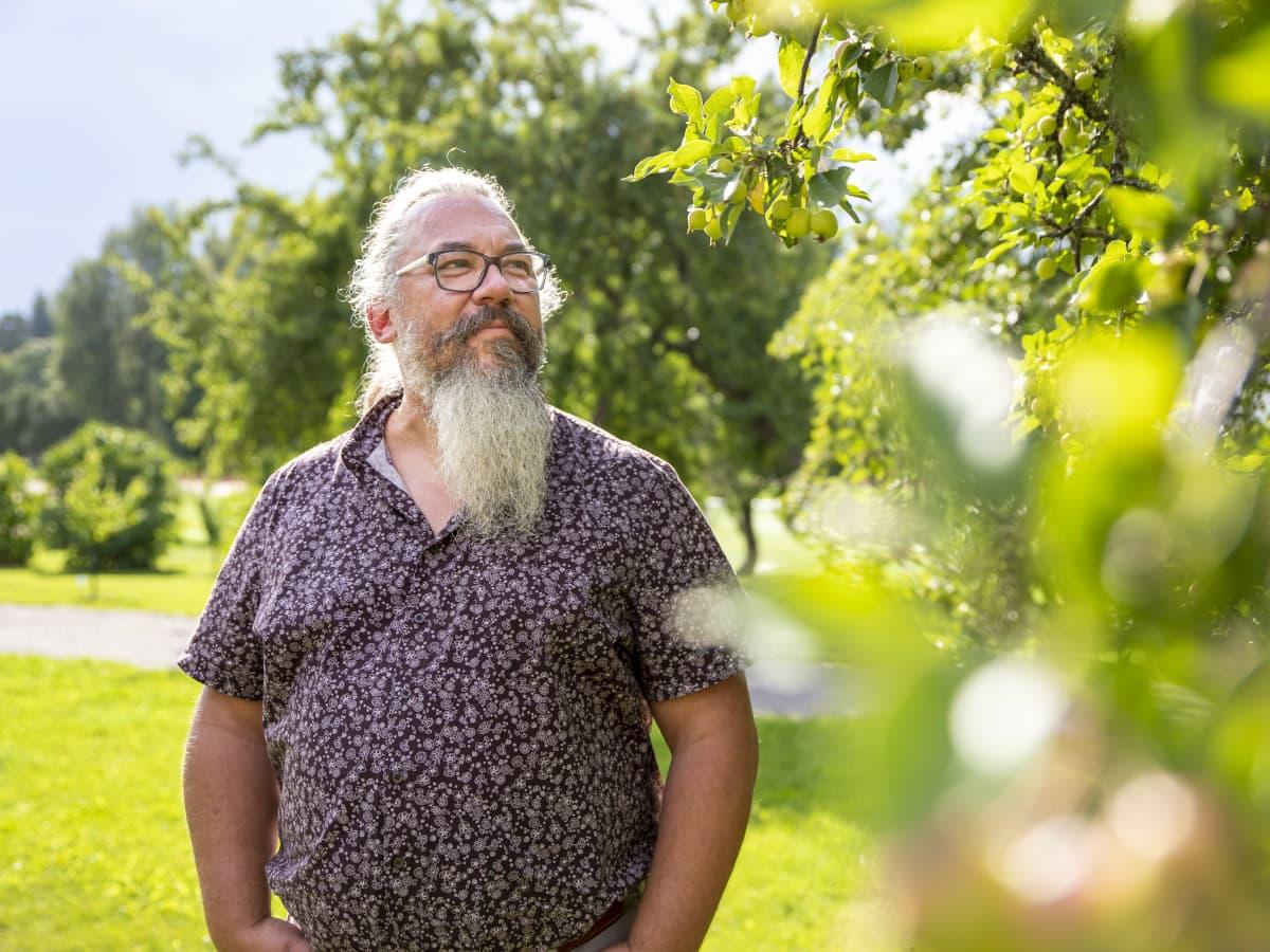 Jyväskylän yliopiston ekologian professori Janne Kotiaho seisoo omenapuun vierellä.