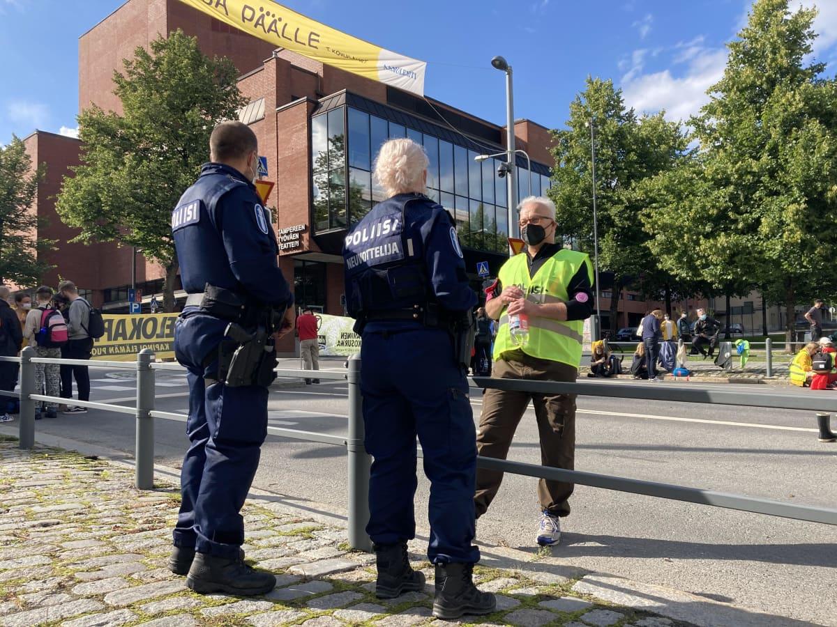 Elokapinan mielenosoittaja Risto Lemmetti puhuu kahden poliisin kanssa mielenosoituksessa.