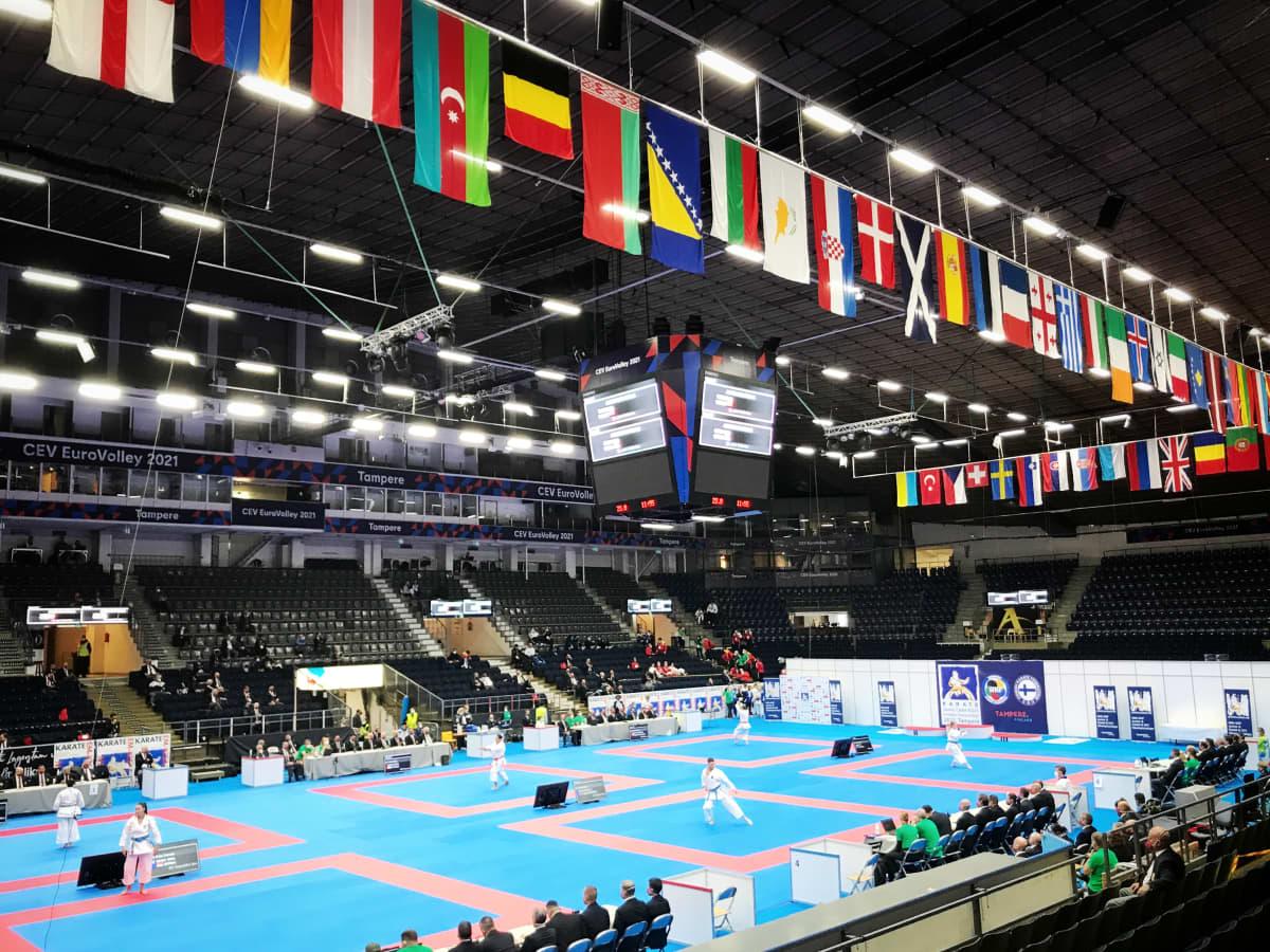 Nuorten EM-karatekisat Tampereella Hakametsän hallissa. Hallin katossa paljon eri maiden lippuja. Karatekat sinisellä matolla.