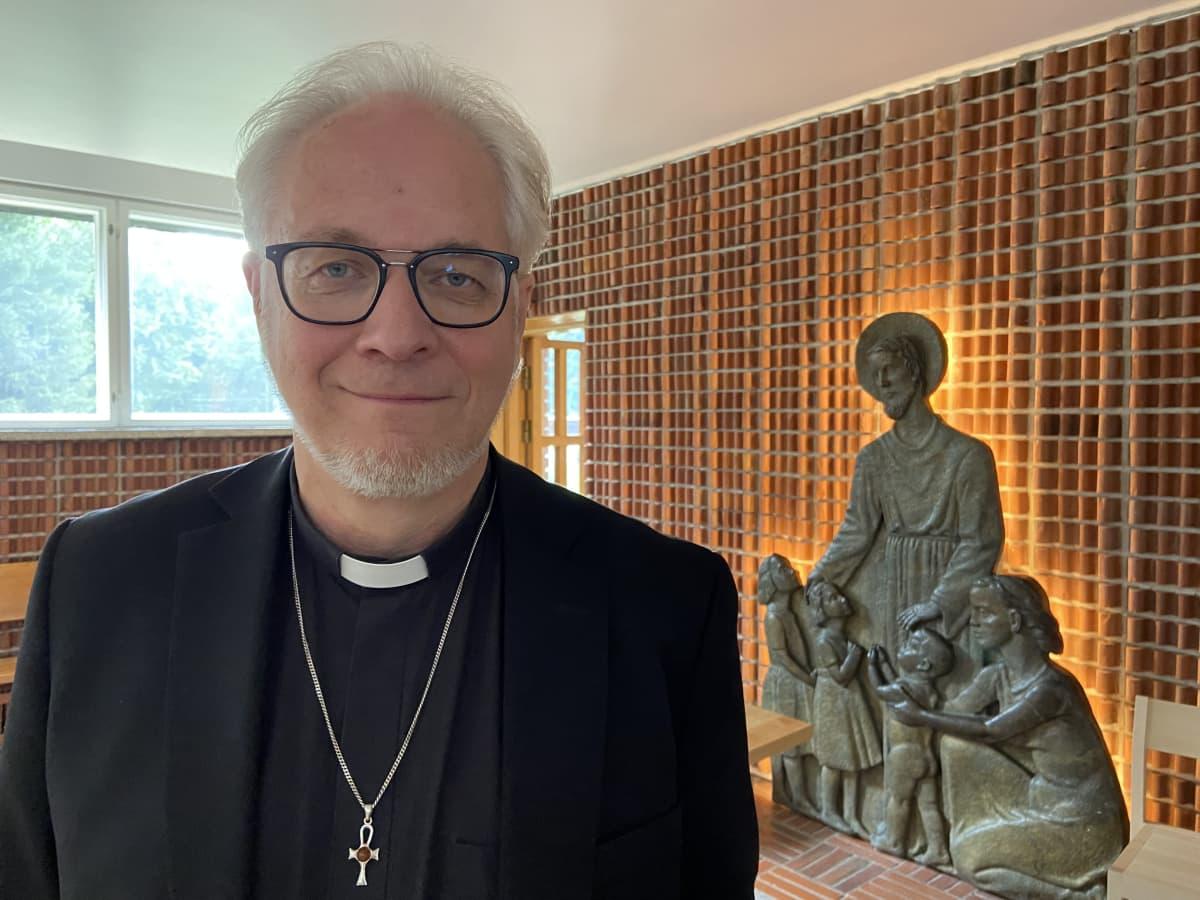 Kirkkoherra Jouko Ala-Prinkkilä Kauhajoen kirkossa. Taustalla Eino Räsäsen reliefi Jeesus siunaa lapsia.