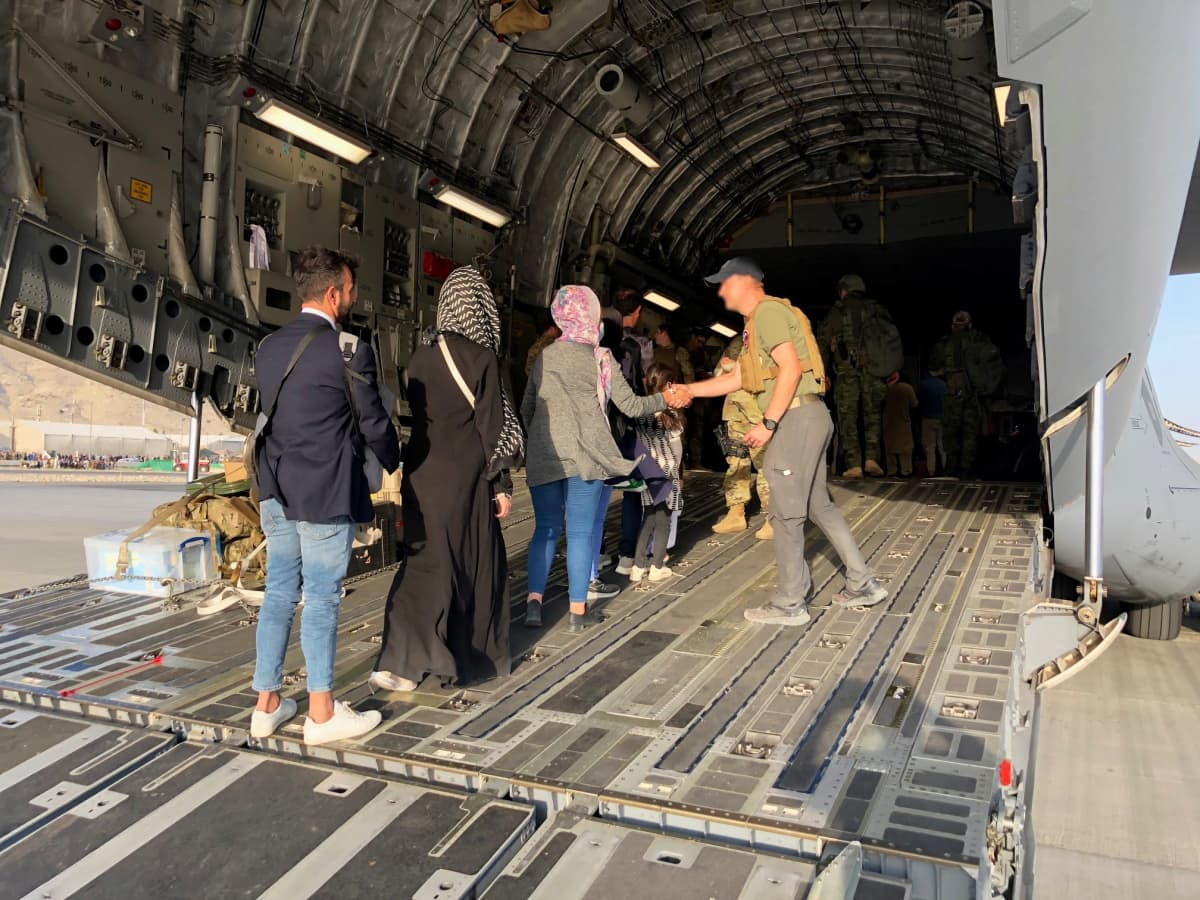 En soldat hjälper människor ombord på ett flygplan.