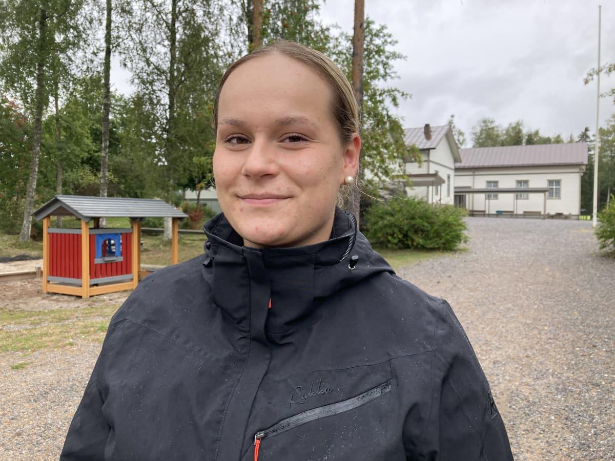 Mustasaarelainen Paula Jaskari seisoo vanhan koulunsa pihalla.