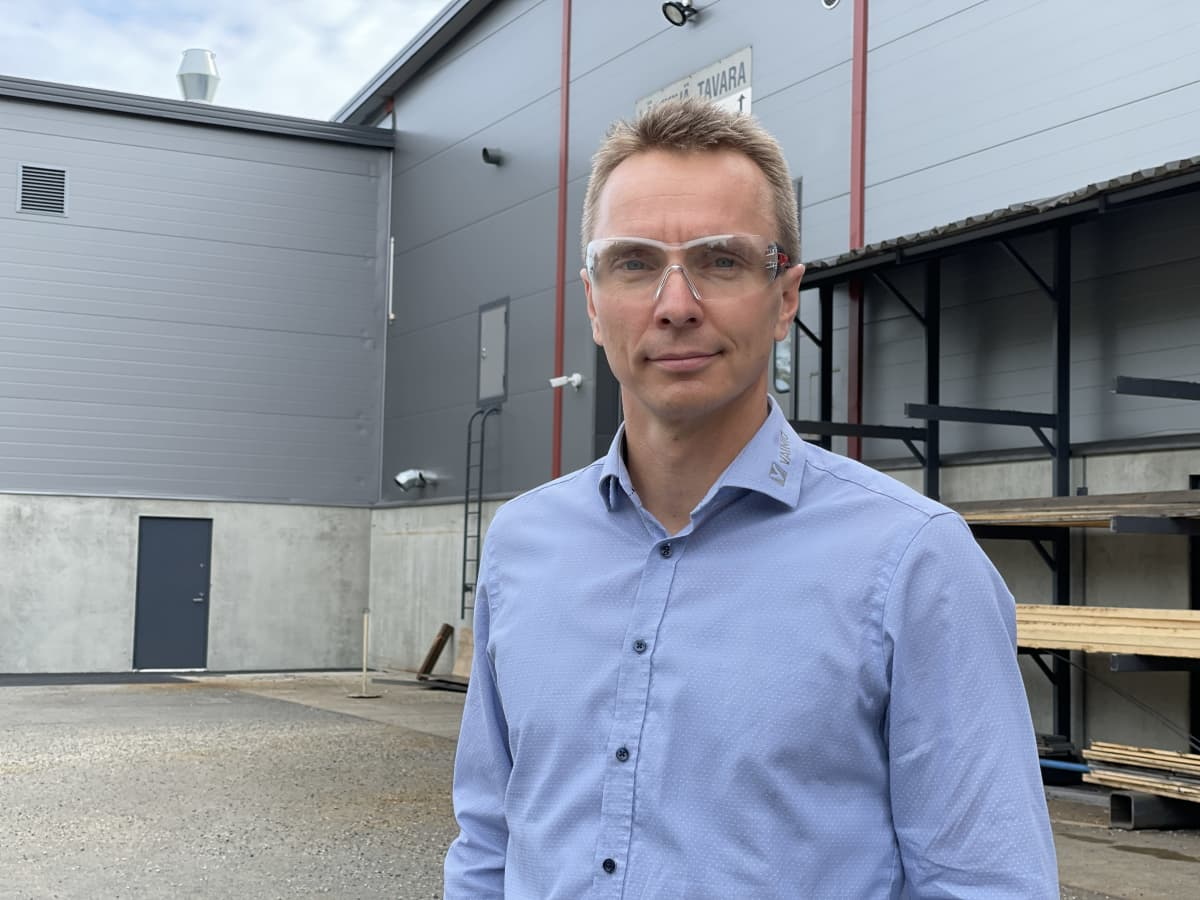Toimitusjohtaja Tommi Lähteinen seisoo hallin edessä.