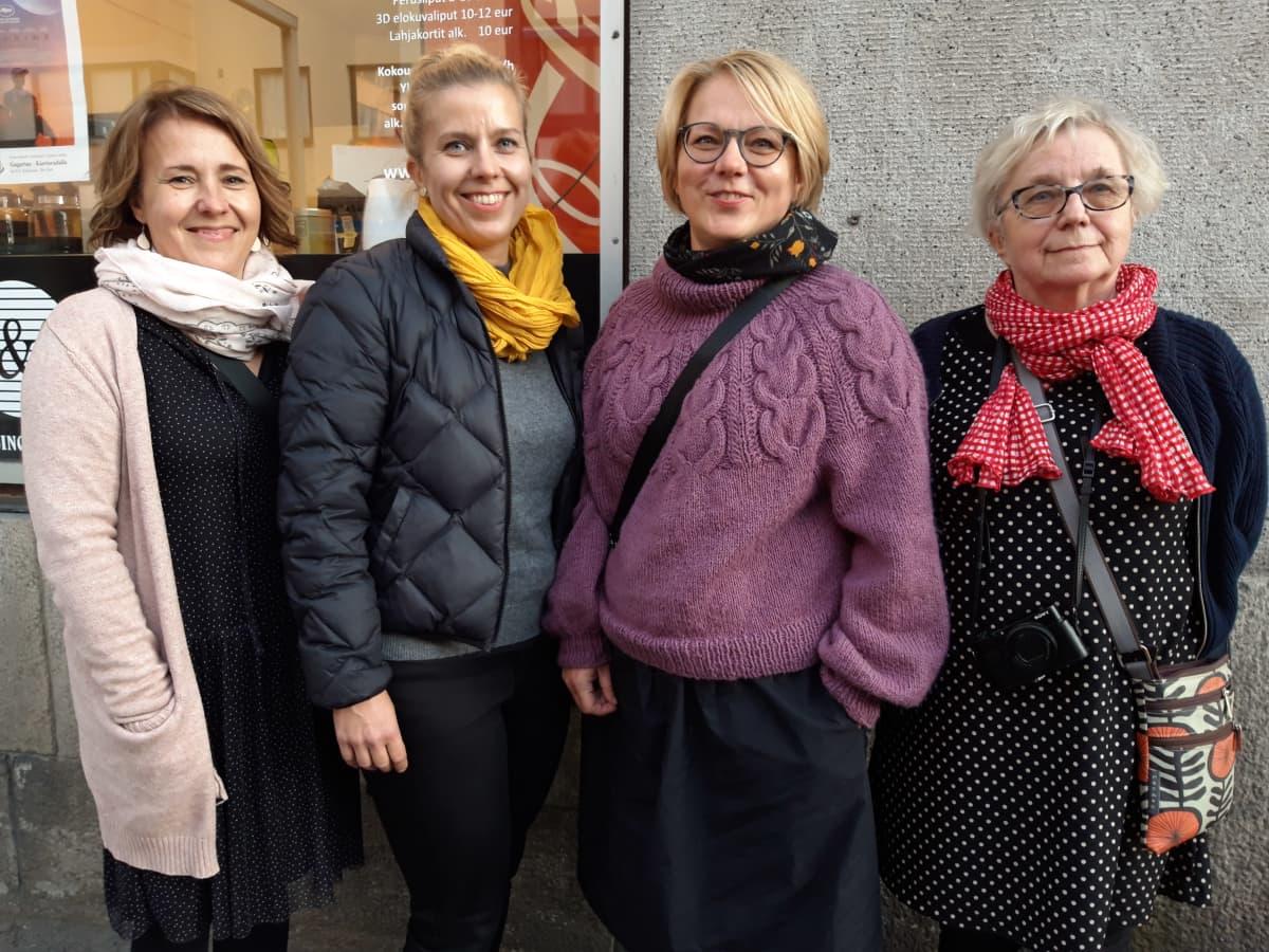Neljä naista seisoo näyteikkunan edessä.