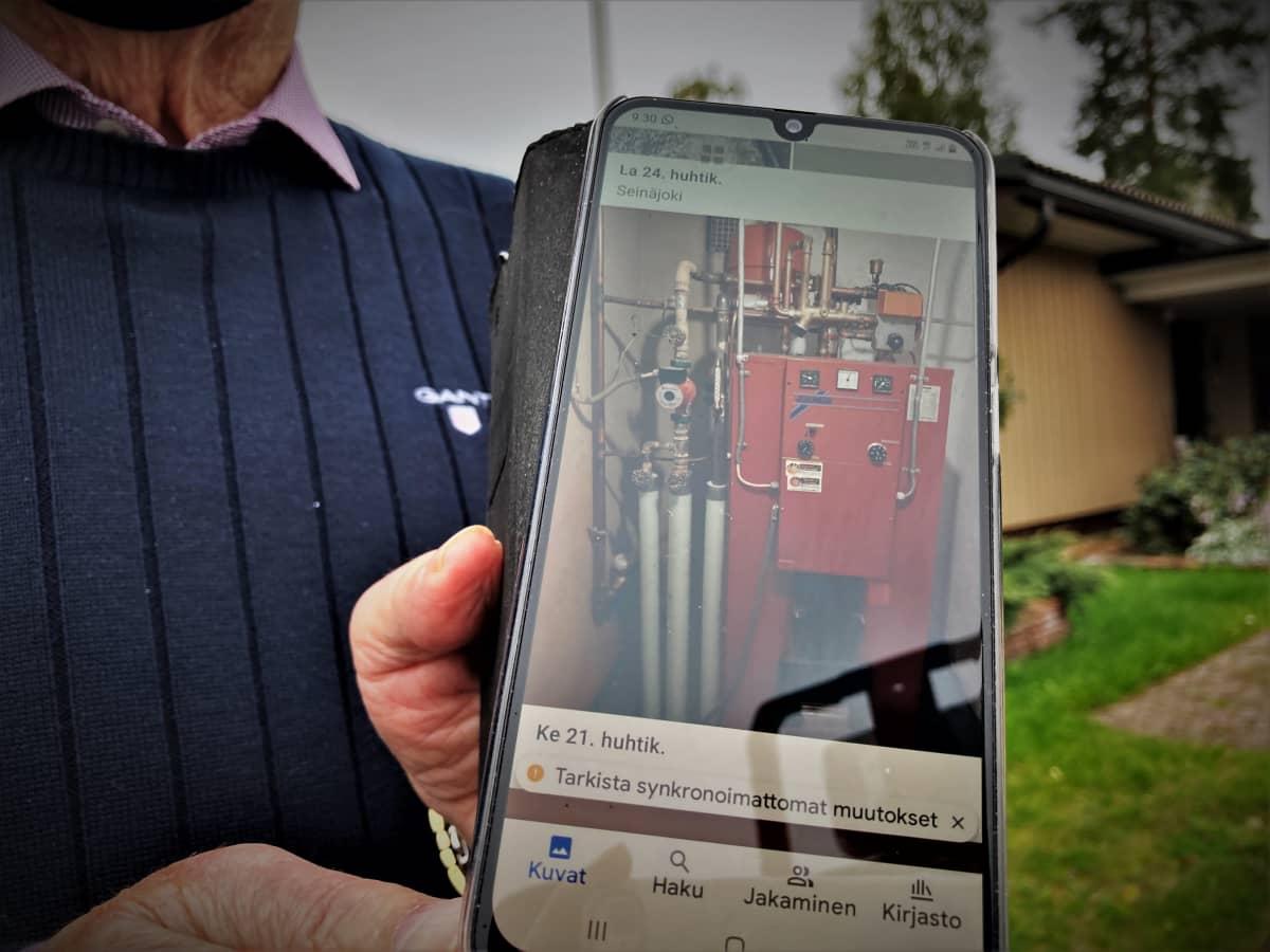Nurmolainen Pentti Niemistö esittelee vanhaa öljykattilaa kännykän kuvasta.
