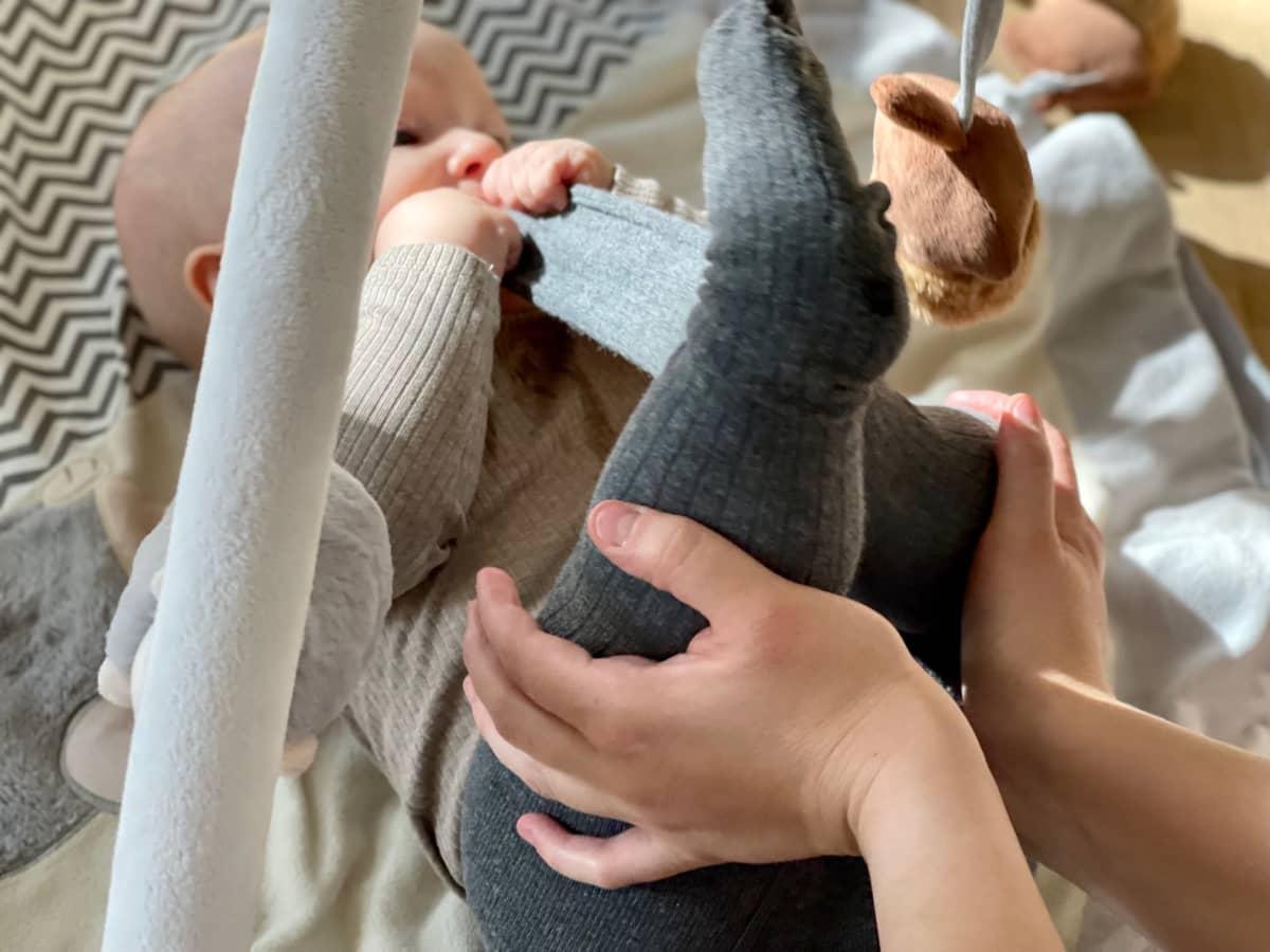 Naisen kädet pitelevät vauvan jalkoja. Vauva makaa selällään viltillä leikkikehässä lattialla.