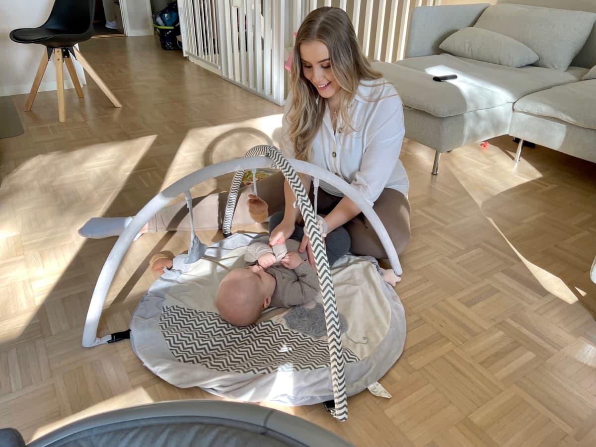 Äiti istuu olohuoneen lattialla ja leikkii viltillä selällään makaavan vauvan kanssa.