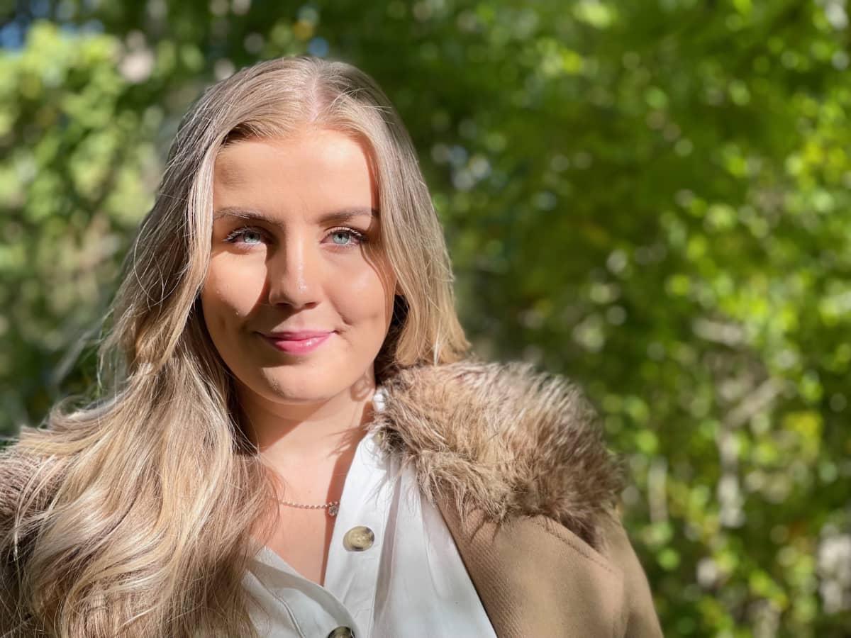 Vaalearuskeahiuksinen nainen katsoo intensiivisesti kameraan sinisillä silmillään. Aurinko tuo valoa kasvoille, taustalla vihreä maisema.
