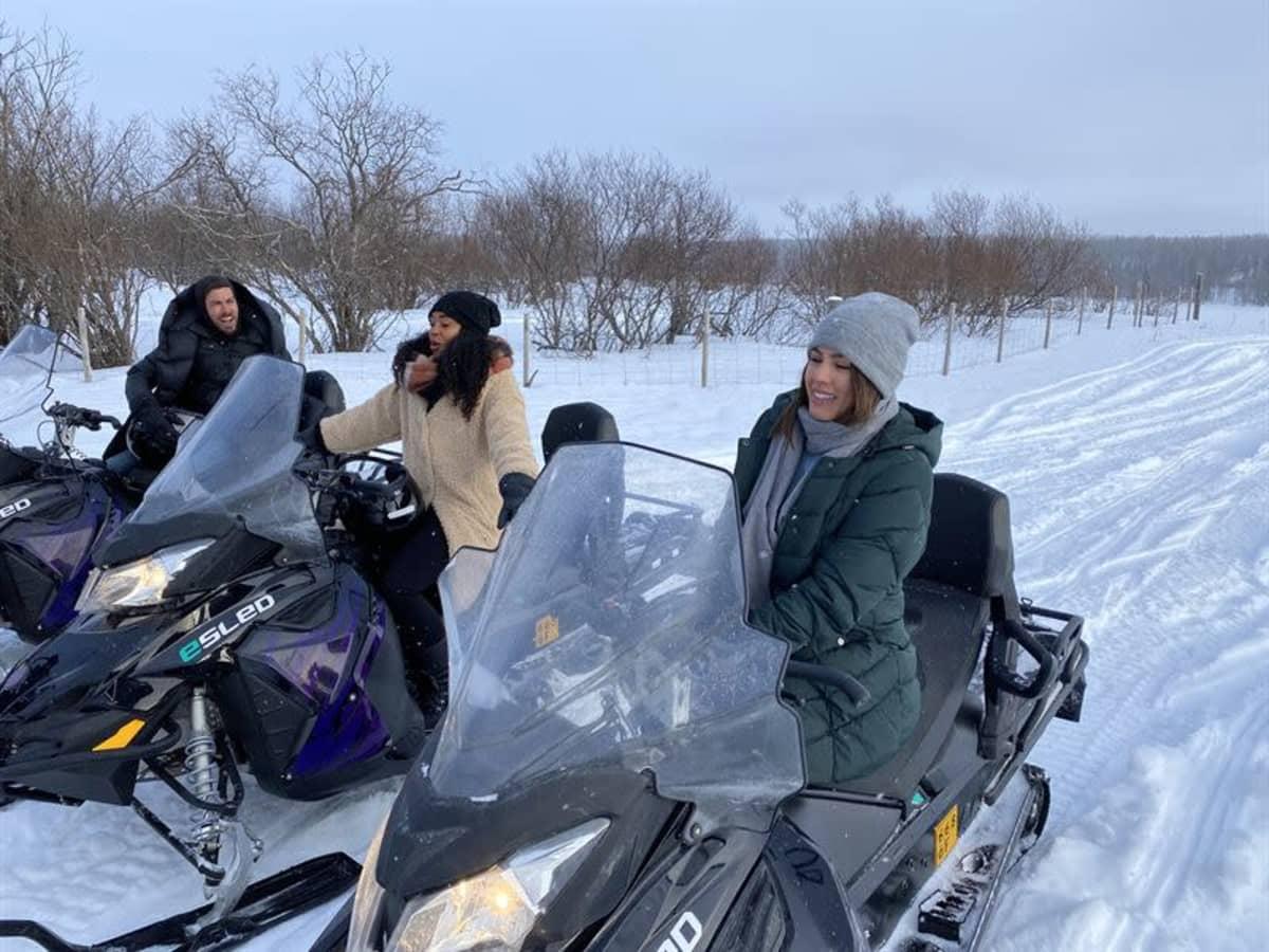 Ihmisiä istuu moottorikelkkojen päällä lumisessa maisemassa.