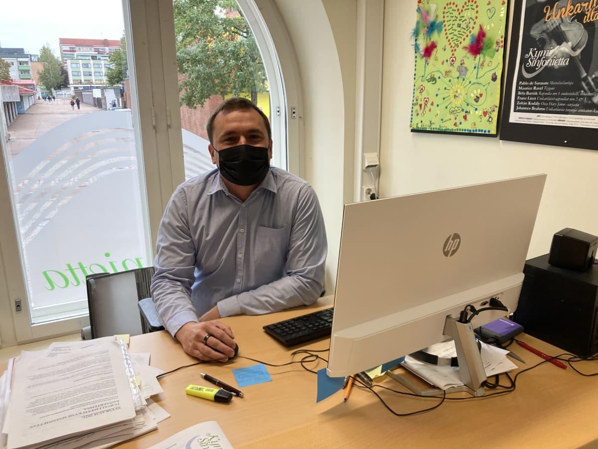 Kauluspaitaan pukeutunut mies istuu työpöytänsä ääressä tietokoneen hiiri kädessään