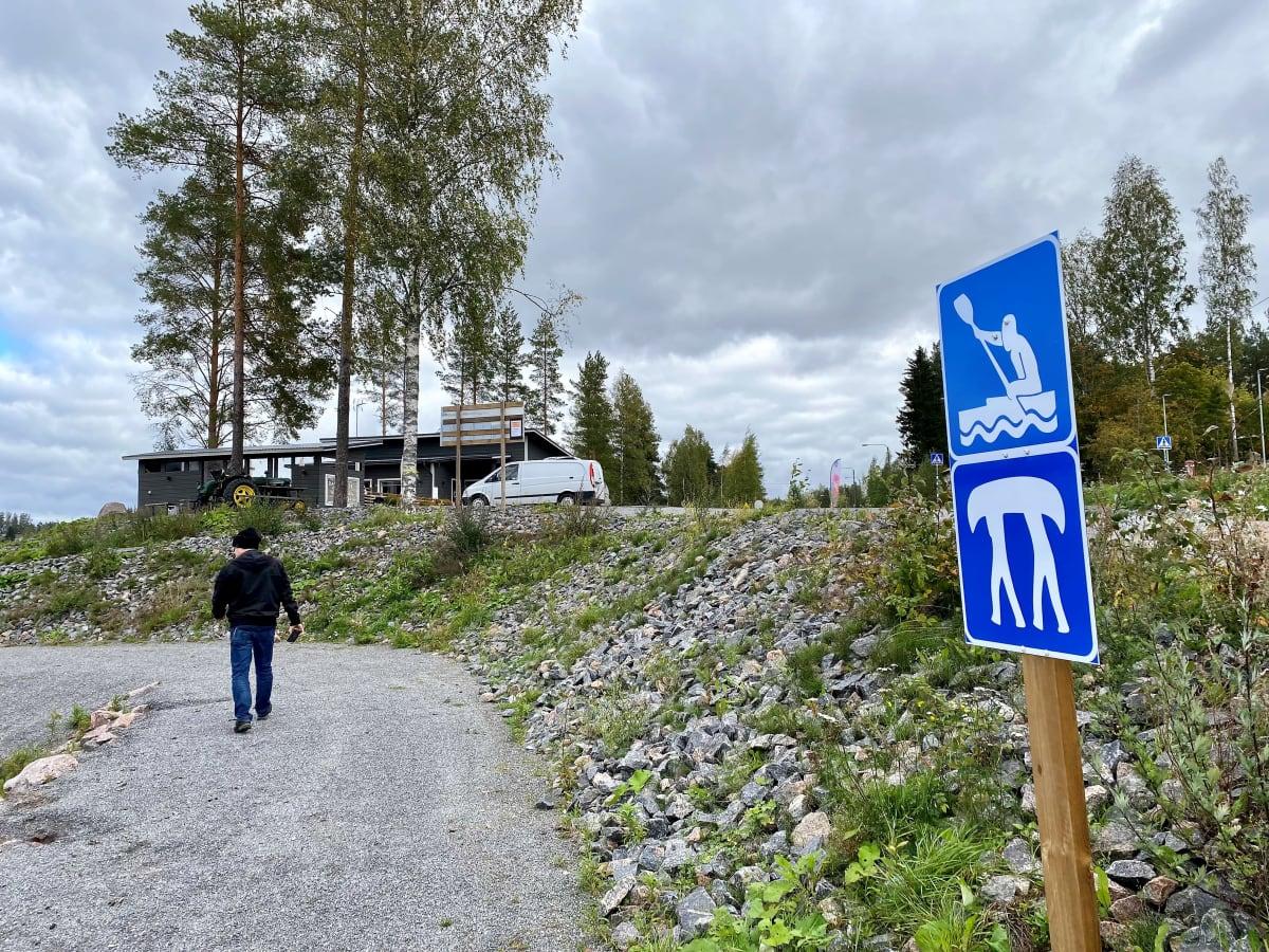 Melontaopaste Iitin Vuolenkoskella, Rantamestan rannassa. Mies kävelee rannasta kohti taustalla kohavaa rakennusta.