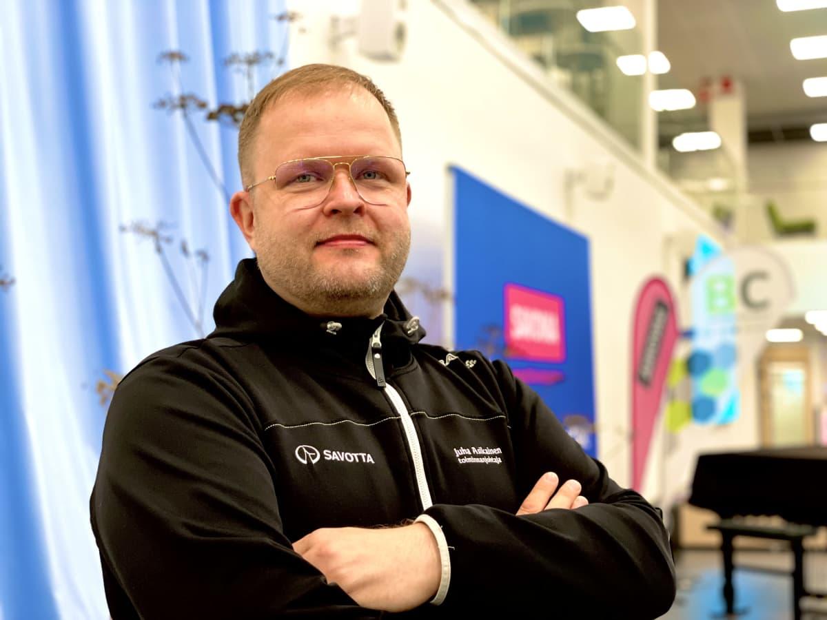 Juha Asikainen seisoo kädet puuskassa oppilaitoksen aulatilassa.