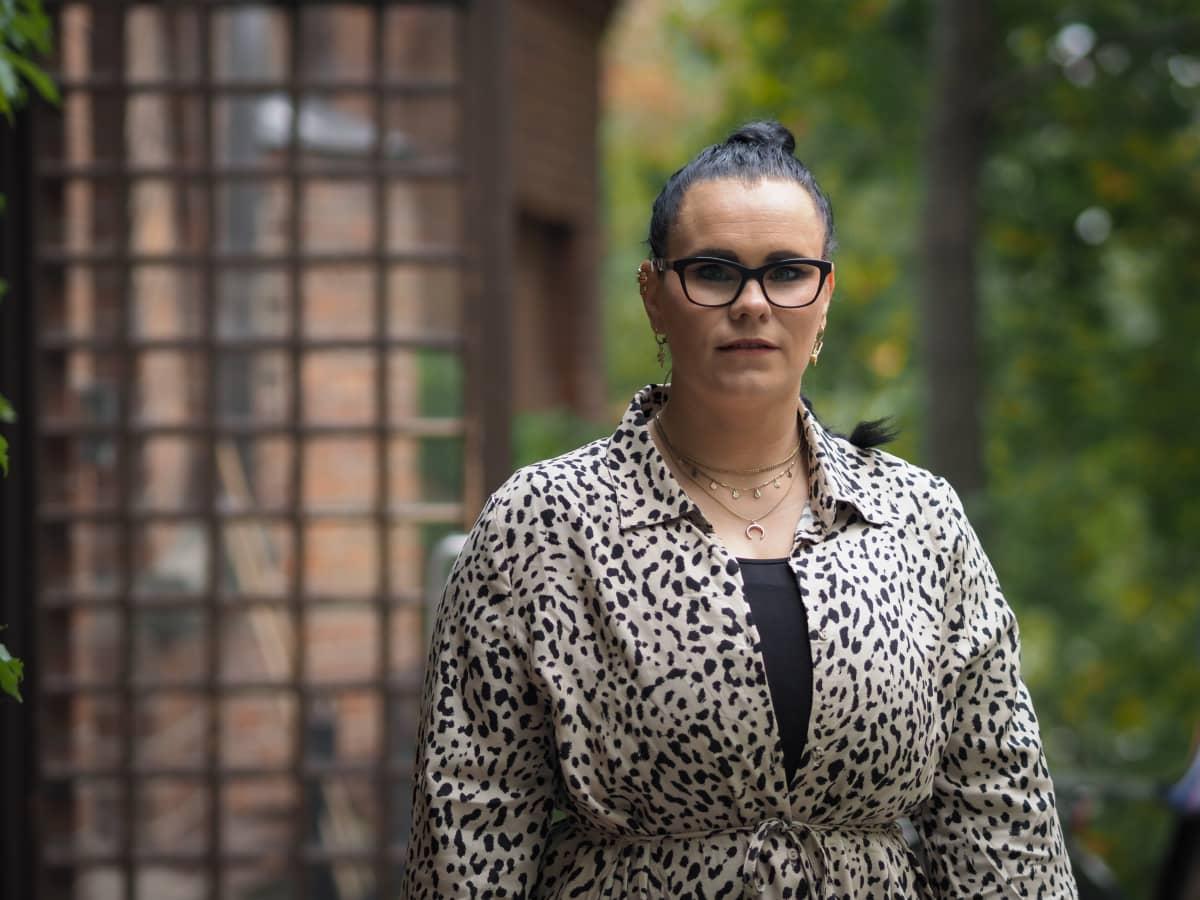 Tummahiuksinen nainen puolikuvassa Tampereen G Livelabin etuoven edessä.