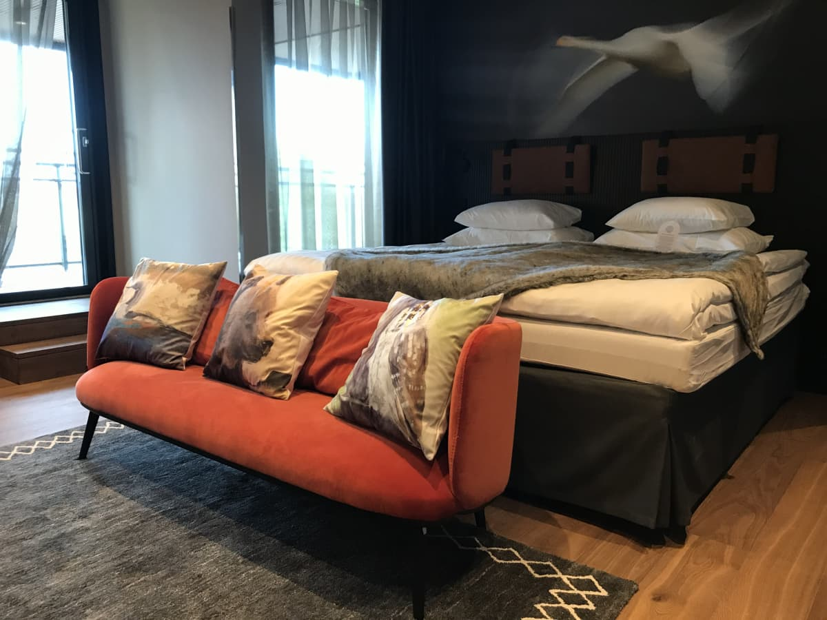 Uudistettu hotellihuone, jossa on punainen sohva ja muhkea sänky.