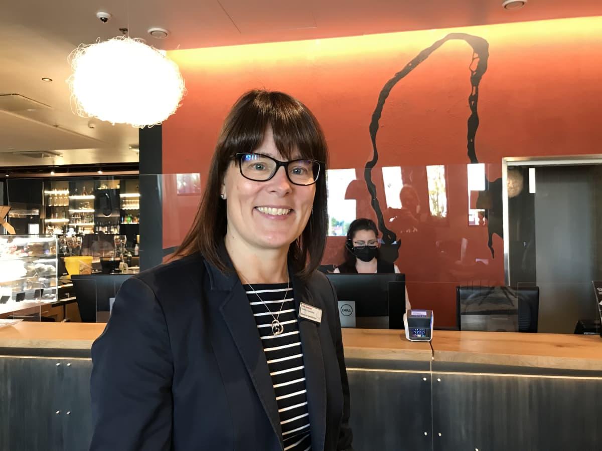 Tummahiuksinen ja silmälasipäinen nainen seisoo hotellin vastaanotossa.