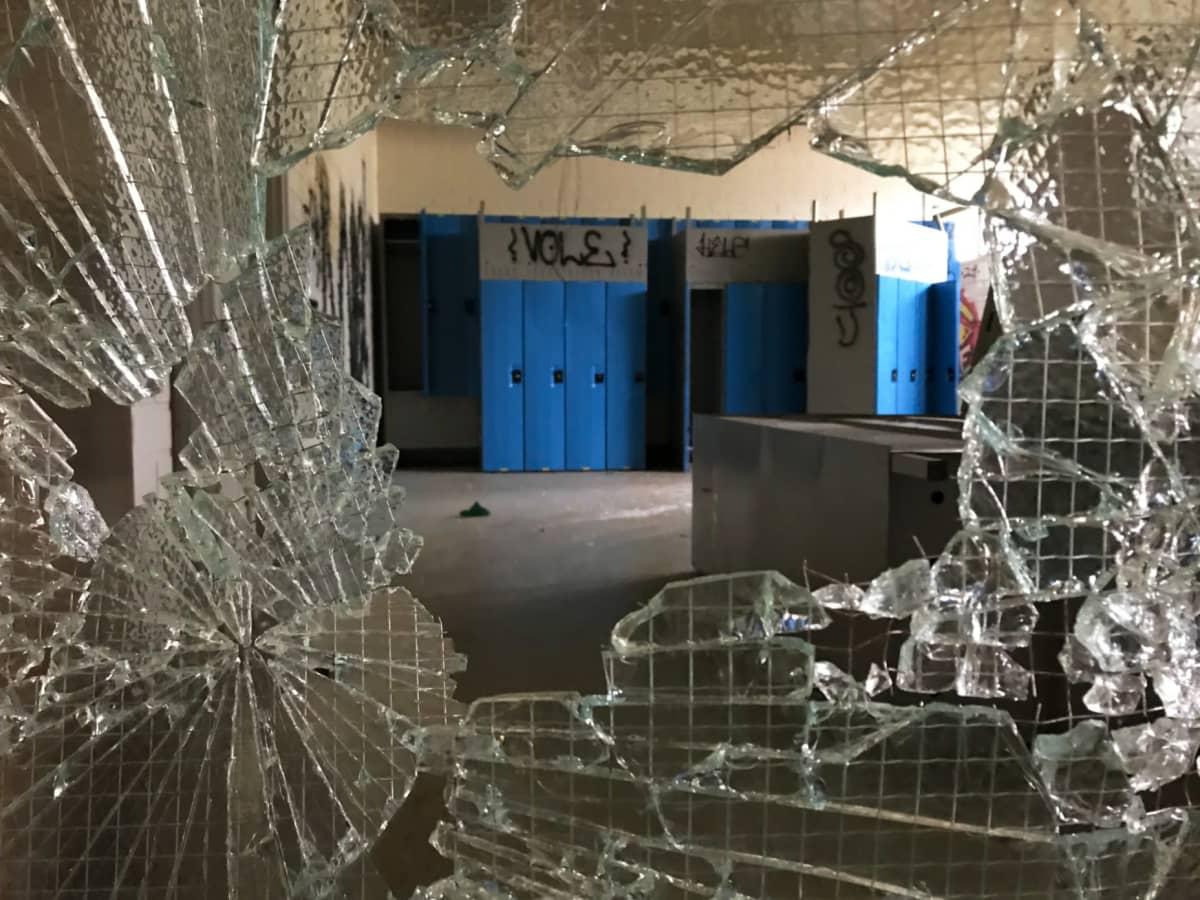 Rikottu lasiovi Kontiorannan varuskunnan vanhassa uimahallissa.