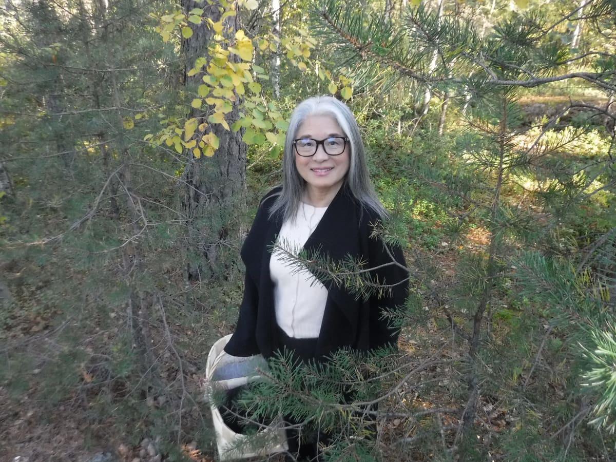 Naomi Moriyama seisoo syksyisessä metsässä kori kädessään