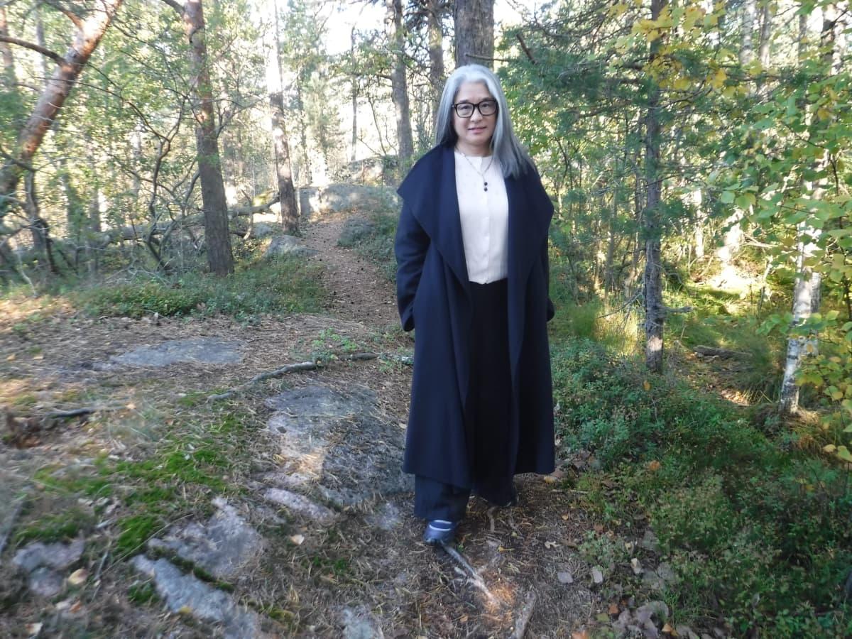 Nainen seisoo syksyisessä metsässä