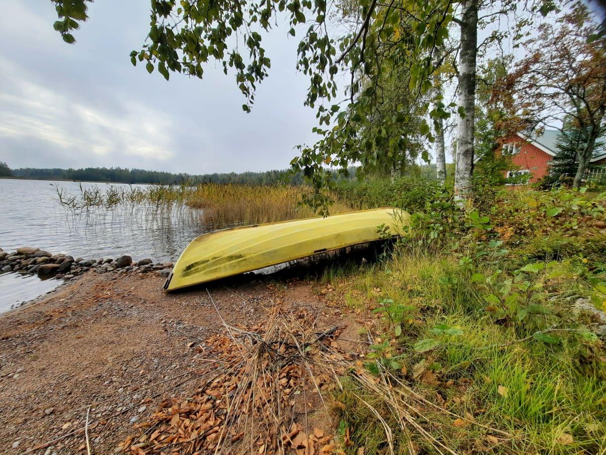 Keltainen soutuvene kumollaan kesämökin rannassa