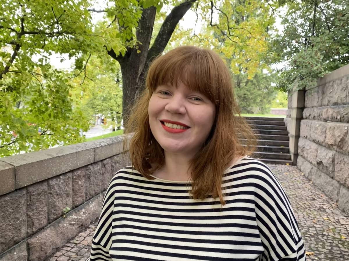 Mustavalkoraitaisessa paidassa poseeraava, punatukkainen nainen
