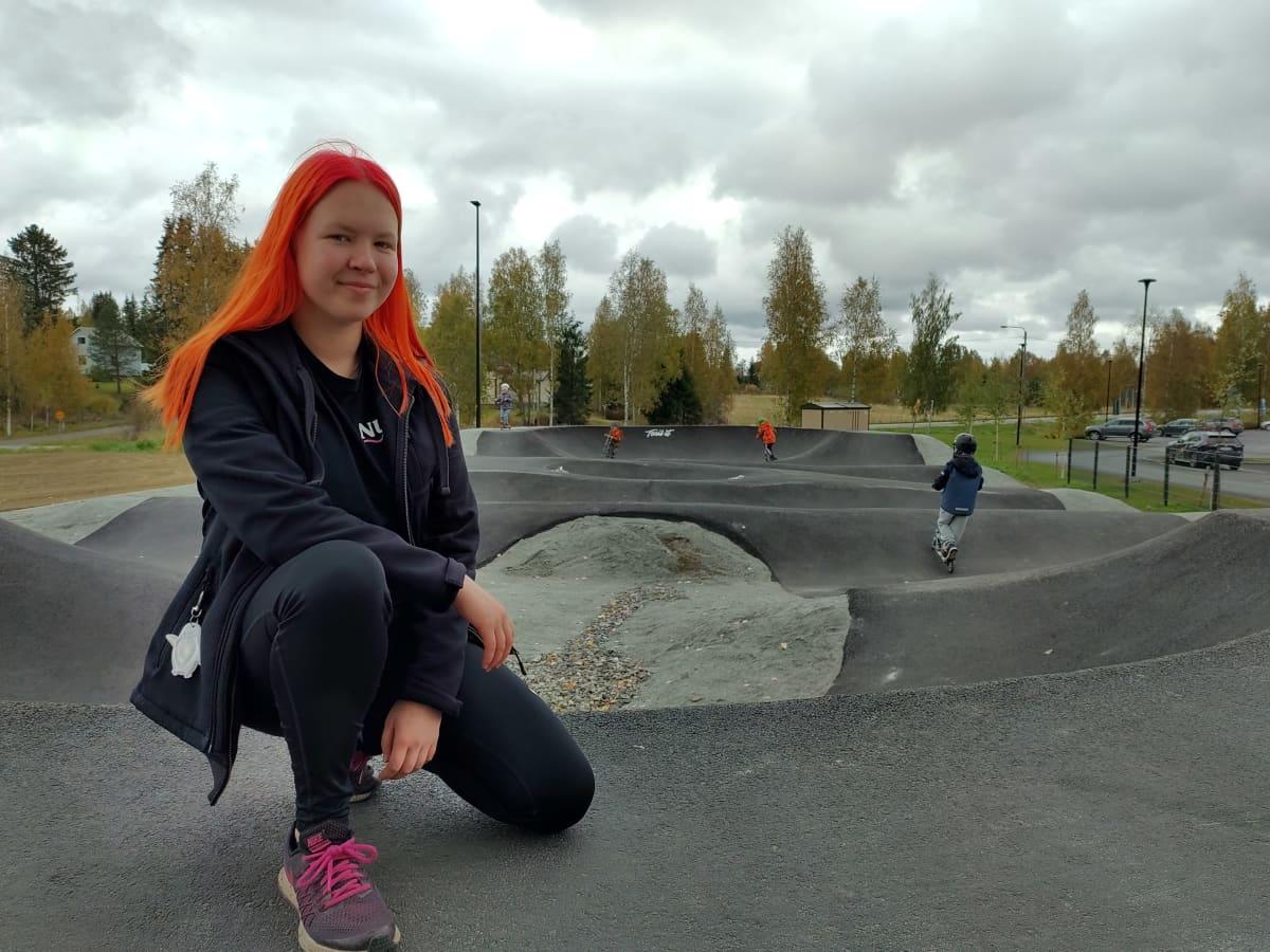 Polvijärven nuorisovaltuuston puheenjohtaja Inka Mustonen kunnan uudella pumptrack-radalla. Taustalla radalla potkulautailevia lapsia.