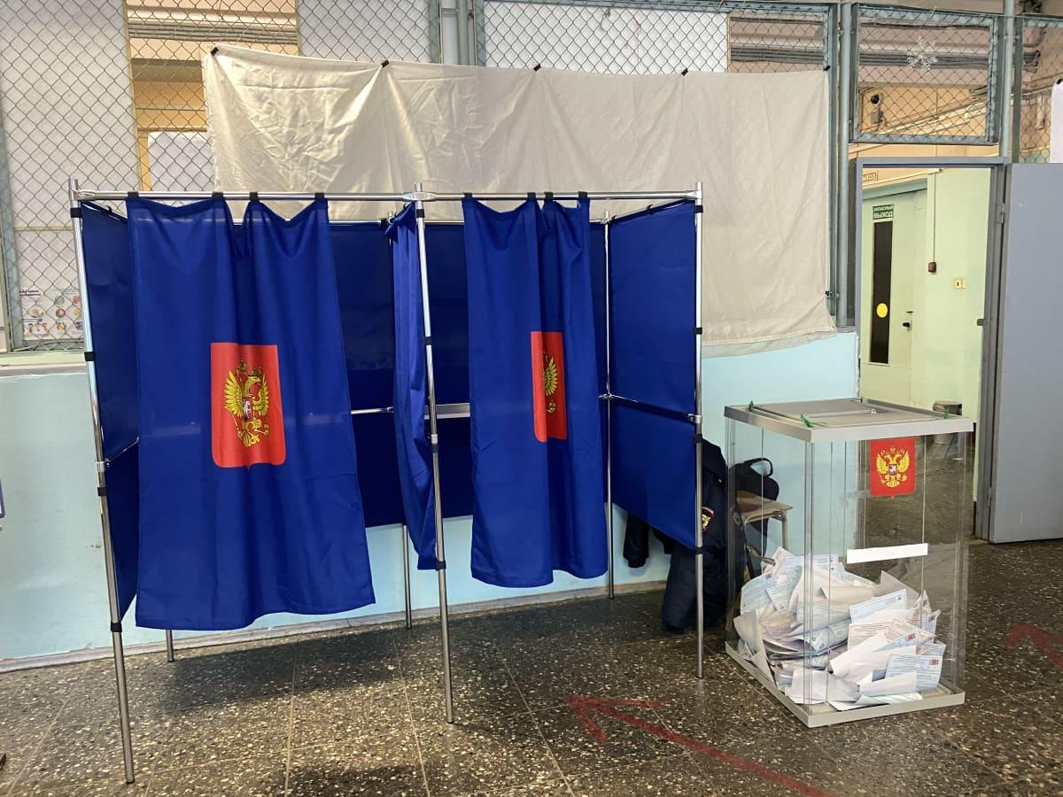 Kaksi siniverhoista äänestyskoppia ja läpinäkyvä uurna, jossa vaalilipukkeita.
