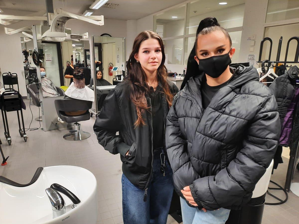 Kaksi nuorta hiusalan opiskelijaa ammattiopiston kampaamossa.