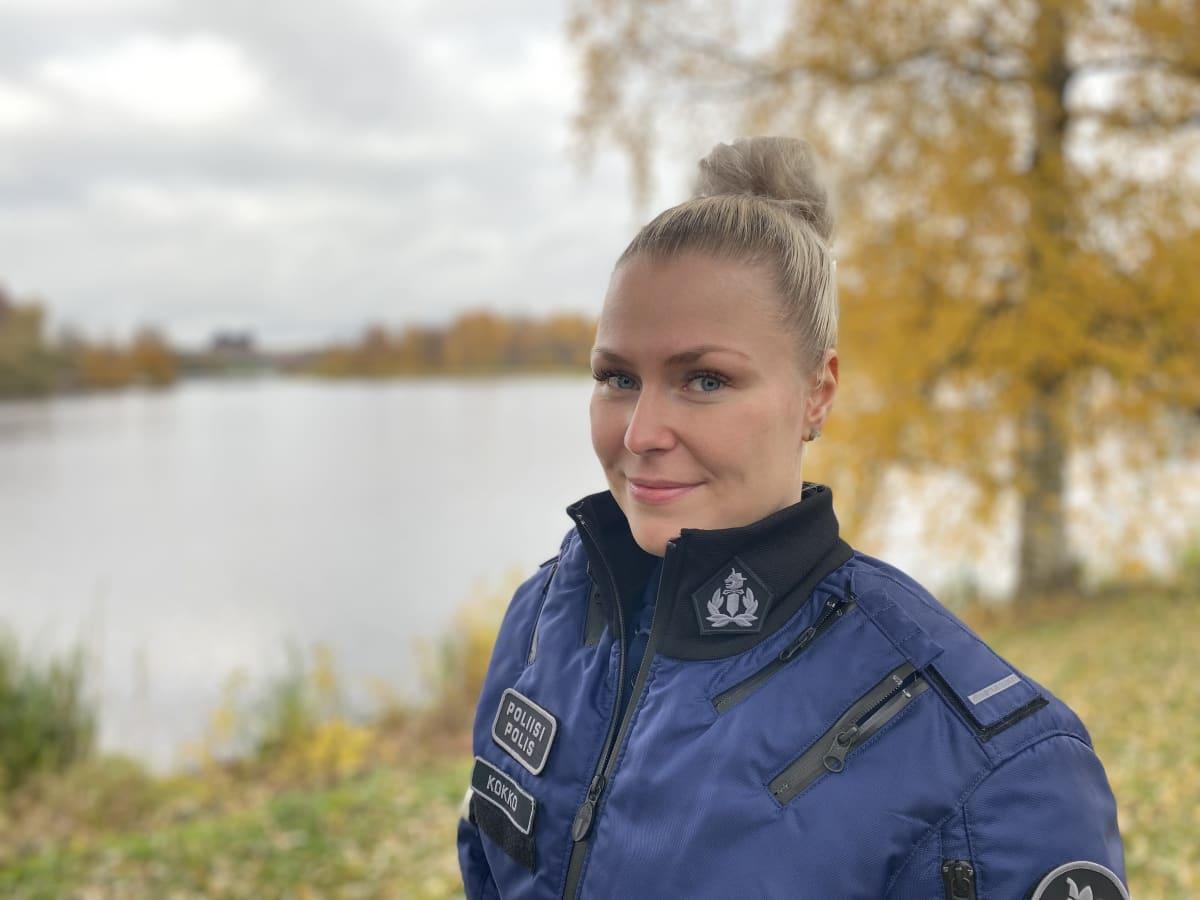 Vanhempi konstaapeli Senni Kokko katsoo virka-asussa hymyillen kameraa. Taustalla ruskan värjäämää nurmikko ja lehtiä sekä järven rantaa. Kuva otettu 8.10.2021 Hämeenlinnassa.