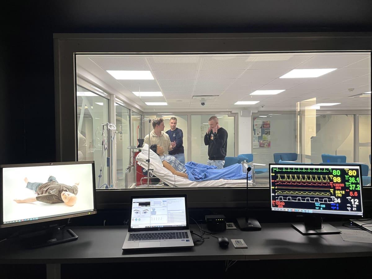 Kolme Kajaanin ammattikorkeakoulussa sairaanhoitajaksi opiskelevaa nuorta miestä on kuvattu simulaatiostudiosta käsin hoitamassa potilasvuoteella makaavaa hoitonukkea.