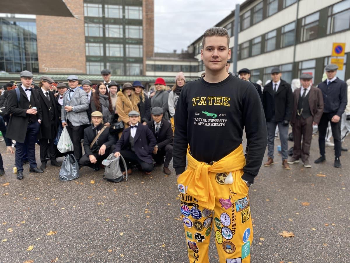Nuori mies keltaisissa haalareissa edustalla, takana joukko vanhanaikaisesti pukeutuneita miehiä ja naisia.