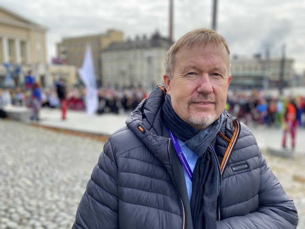 Vanhempi sinisessä untuvatakissa Tampereen keskustorilla, Katsoo kameraan.
