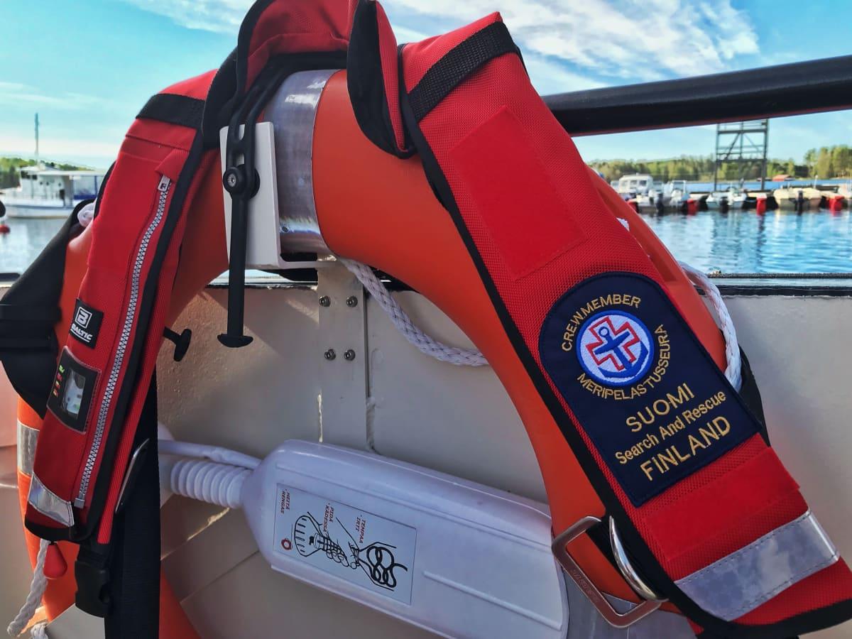 Suomen Meripelastusseuran logolla varustetut pelastusliivit pelastusrenkaan päällä.