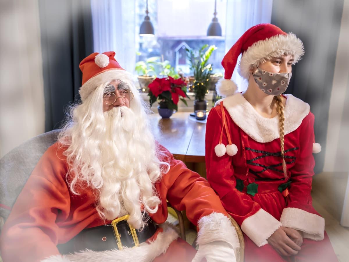 Joulupukki ja tyttötonttu, jolla on kasvomaski, istuvat olohuoneessa.