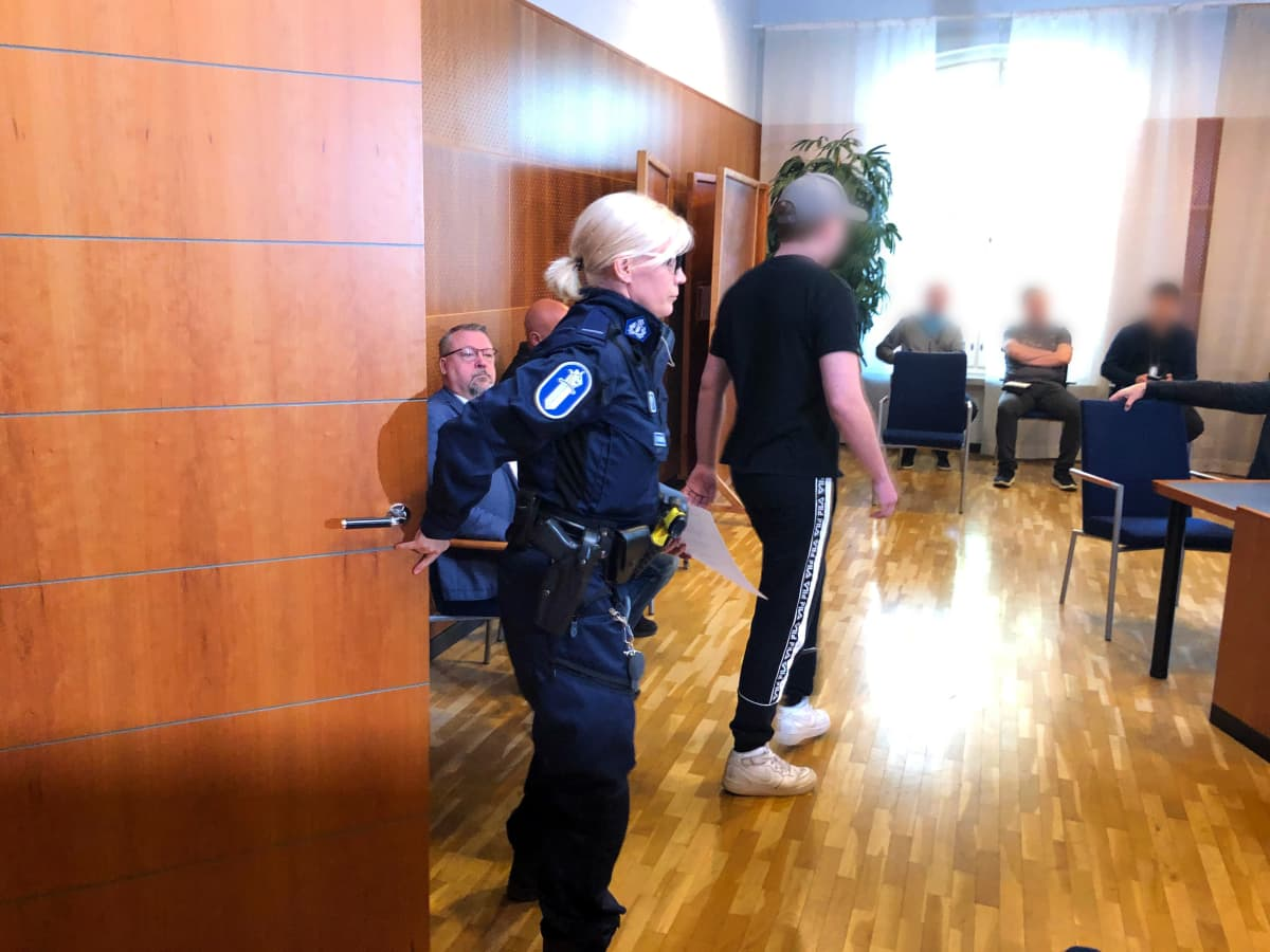 Poliisi tuo murhasta syytettyä uhrin poikaa oikeussaliin Tampereen oikeussalissa.